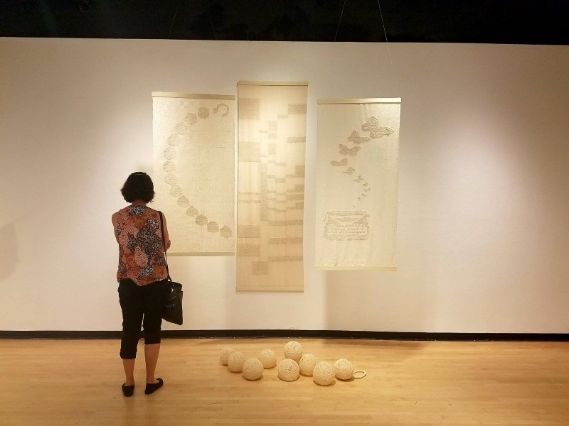"Arnold stands in front of one of the group fiber art displays, which she described as ""peaceful"" and ""nostalgic."
