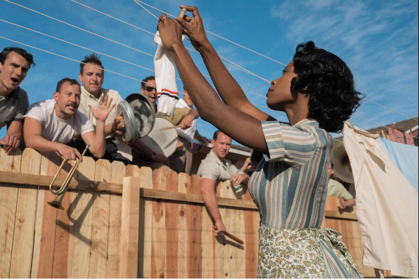 A Black American woman is seen holding up her laundry, as a group of white men holler at her over a wooden fence.