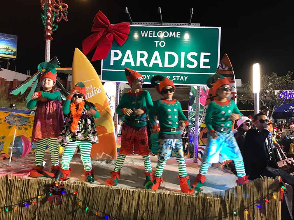 Children in elf costumes dancing on top of a parade float.