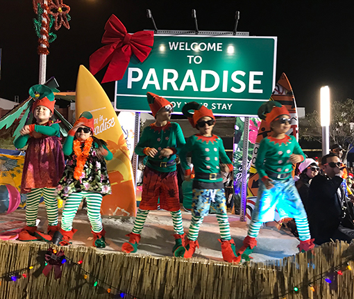 Children in Christmas elf costumes dancing on top of a parade float.