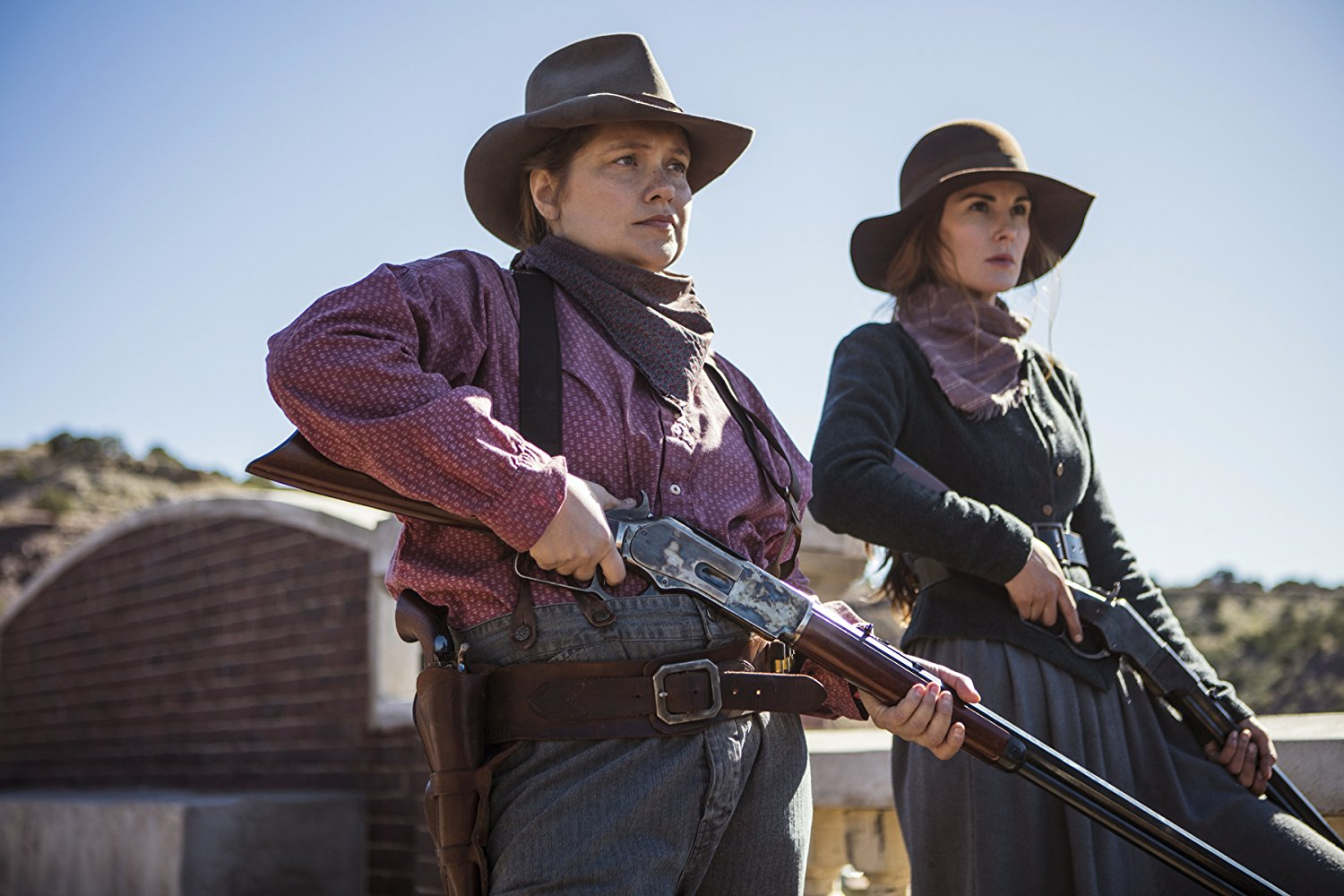 Two women in cowboy attire, holding shotguns.