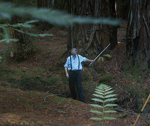 A blind man in a forest with a camera set up beside him.