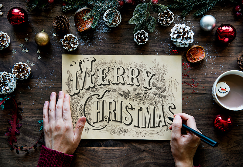 Someone using calligraphy to create a Holiday card.