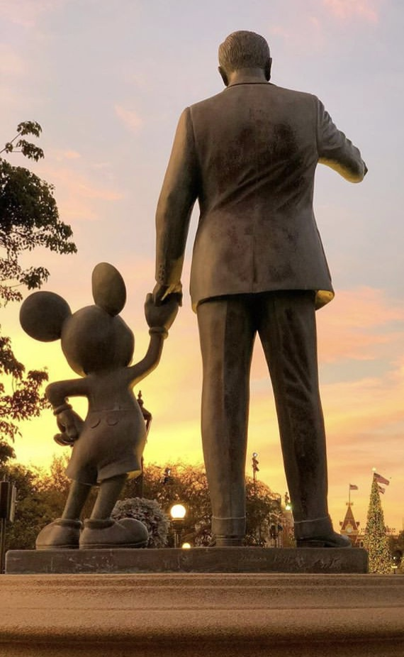 Statue of Walt Disney holding Mickey's hand at sunset