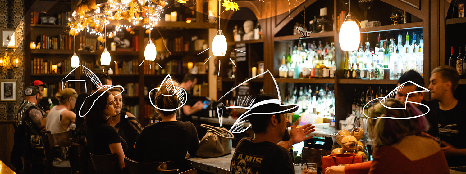 People in a spooky bar with witch hats drawn on their heads.