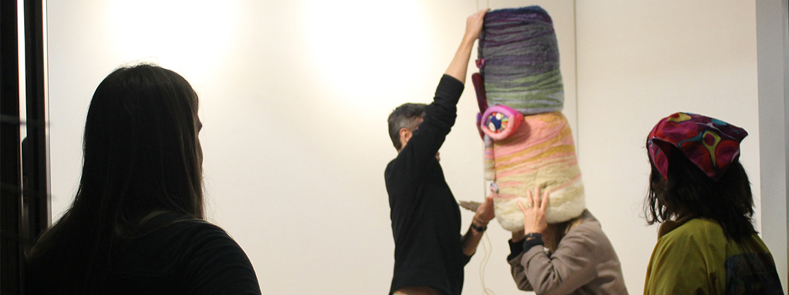 Aaron Brown (left) watches as guests try on his untitled wearable sculpture.